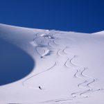Snowboarders riding the Rainbow north glacier run